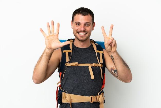 Brazylijski alpinista z dużym plecakiem na białym tle, licząc siedem palcami