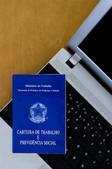 Brazylijski dokument ubezpieczenia społecznego na komputerze, drewniany stół w tle