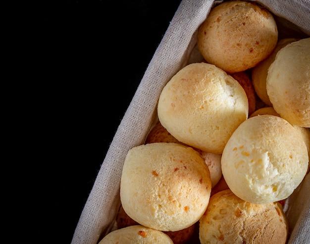 Brazylijski domowy chleb serowy, aka 'pao de queijo' w rustykalnym koszu.