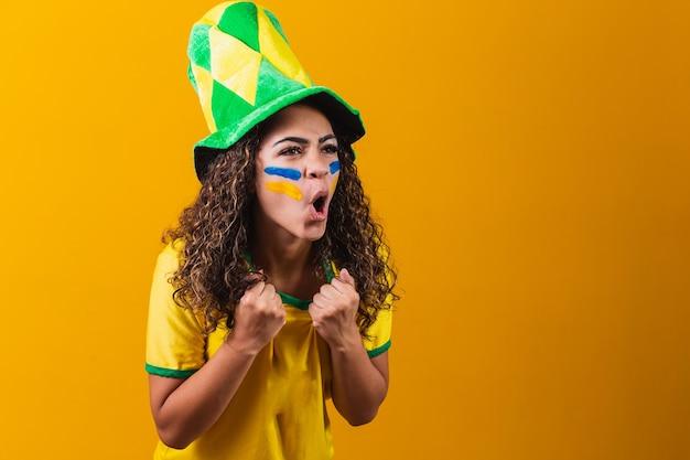 Brazylijski fan. brazylijski fan świętuje mecz piłki nożnej lub piłki nożnej na żółtym tle. kolory brazylii.