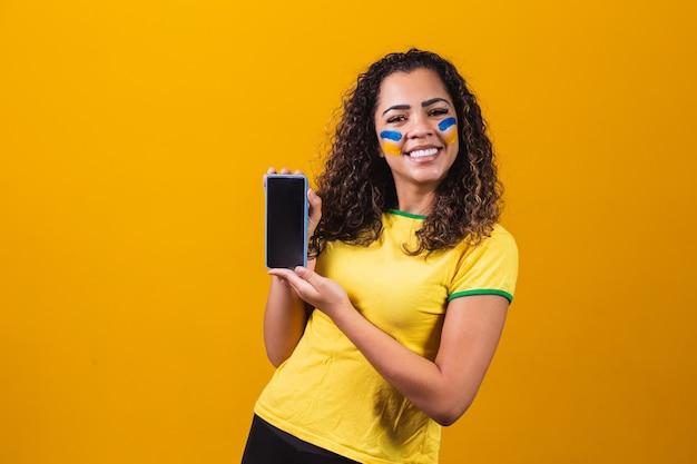 Brazylijski fan trzymający smartfon z miejscem na kopię