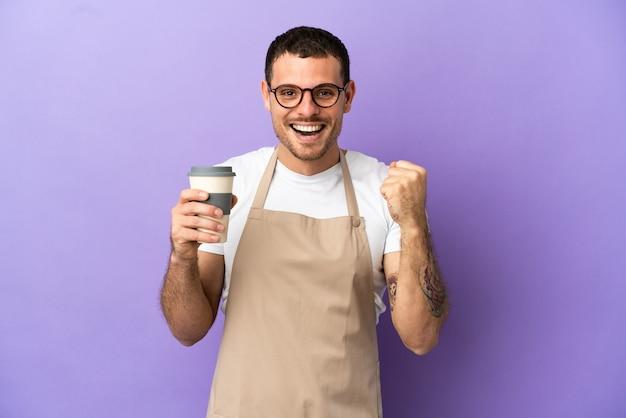 Brazylijski kelner w restauracji na odosobnionym fioletowym tle świętuje zwycięstwo w pozycji zwycięzcy
