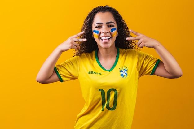 Brazylijski kibic. brazylijska kobieta fan świętuje na mecz piłki nożnej lub piłki nożnej na żółtym tle. kolory brazylii.
