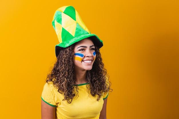 Brazylijski kibic. brazylijski fan świętuje mecz piłki nożnej lub piłki nożnej na żółtym tle z miejsca kopiowania. kolory brazylii.