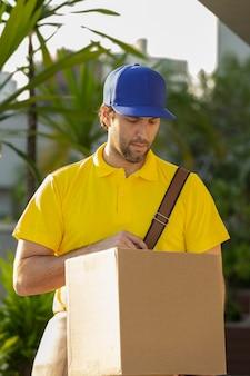 Brazylijski listonosz dostarczający paczkę na ulicy. zakup przez internet jest dostarczany do domu.