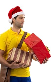 Brazylijski listonosz przebrany za świętego mikołaja dostarcza prezent na białym tle. skopiuj miejsce.