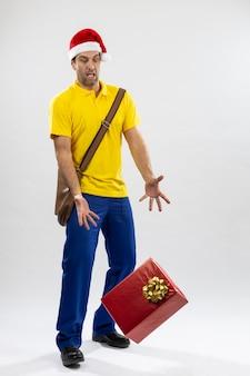 Brazylijski listonosz przebrany za świętego mikołaja upuszczający prezent na białym tle. skopiuj miejsce.