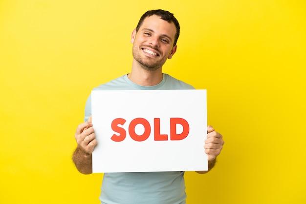 Brazylijski mężczyzna na odosobnionym fioletowym tle, trzymający afisz z tekstem sprzedawany ze szczęśliwym wyrazem twarzy