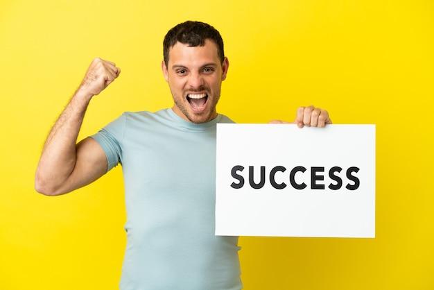 Brazylijski mężczyzna na odosobnionym fioletowym tle, trzymający afisz z tekstem sukces i świętujący zwycięstwo