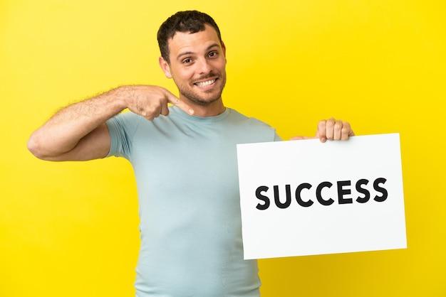 Brazylijski mężczyzna na odosobnionym fioletowym tle, trzymający afisz z tekstem sukces i wskazujący go