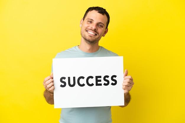 Brazylijski mężczyzna na odosobnionym fioletowym tle, trzymający afisz z tekstem sukces ze szczęśliwym wyrazem twarzy