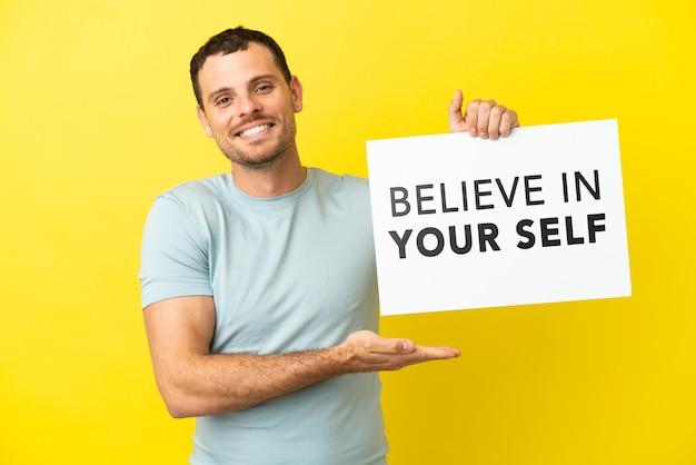 """Brazylijski mężczyzna na odosobnionym fioletowym tle, trzymający afisz z tekstem """"uwierz w siebie"""" i wskazujący go"""