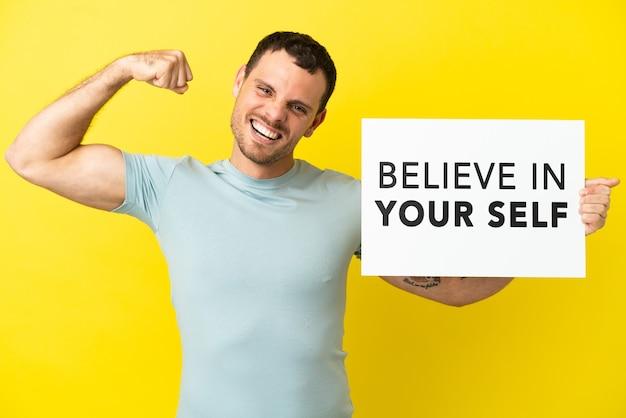 """Brazylijski mężczyzna na odosobnionym fioletowym tle, trzymający afisz z tekstem """"uwierz w siebie"""" i wykonujący silny gest"""