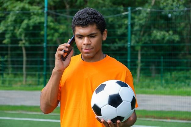 Brazylijski mężczyzna trzymający piłkę nożną i używający smartfona na boisku sportowym