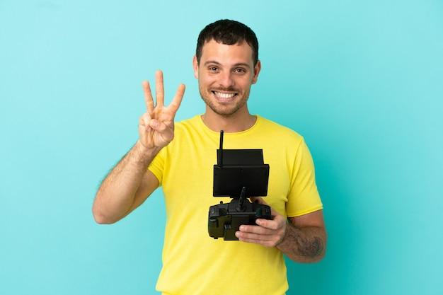 Brazylijski mężczyzna trzymający pilota drona nad odizolowanym niebieskim tłem, szczęśliwy i liczący trzy palcami
