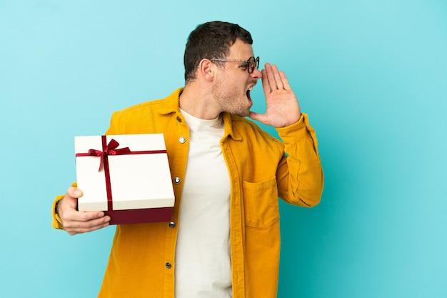 Brazylijski mężczyzna trzymający prezent na odosobnionym niebieskim tle krzyczy z szeroko otwartymi ustami