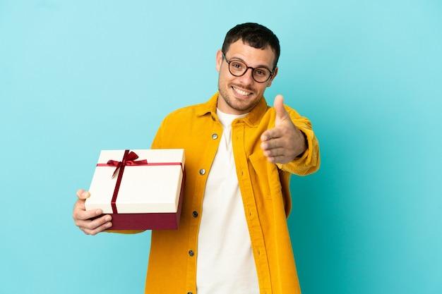 Brazylijski mężczyzna trzymający prezent na odosobnionym niebieskim tle, ściskający dłonie, aby zamknąć dobrą ofertę
