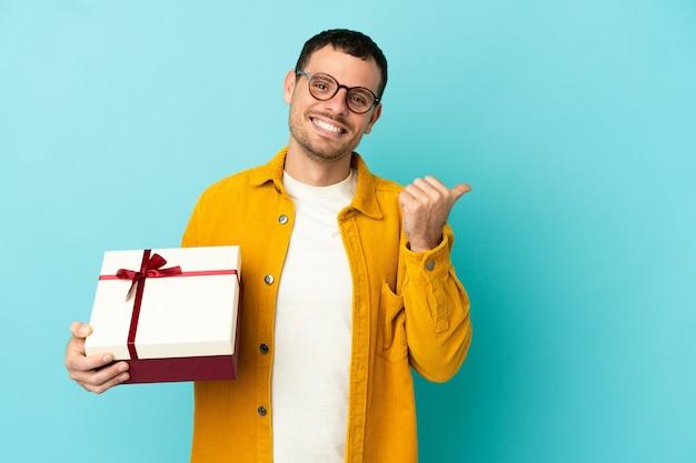 Brazylijski mężczyzna trzymający prezent na odosobnionym niebieskim tle, wskazując na bok, aby zaprezentować produkt