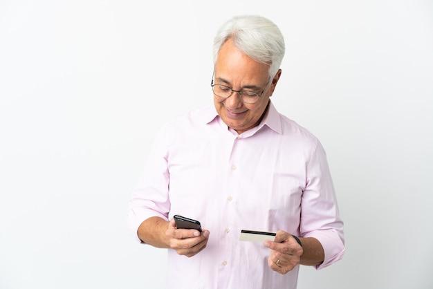 Brazylijski mężczyzna w średnim wieku na białym tle kupując za pomocą telefonu komórkowego za pomocą karty kredytowej