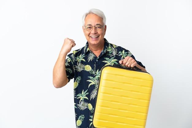 Brazylijski mężczyzna w średnim wieku na białym tle na wakacje z walizką podróżną