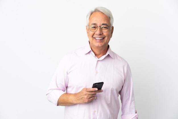 Brazylijski mężczyzna w średnim wieku na białym tle przy użyciu telefonu komórkowego