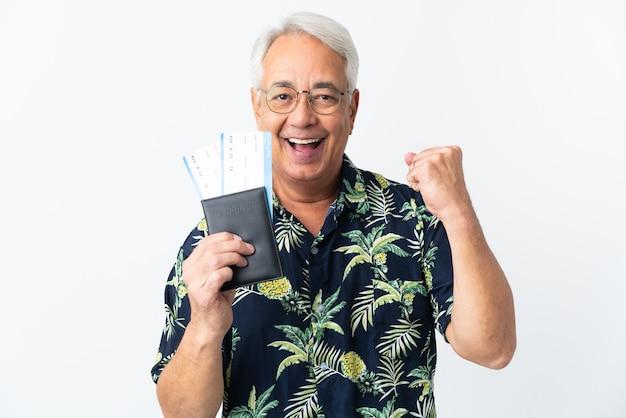 Brazylijski mężczyzna w średnim wieku na białym tle szczęśliwy na wakacjach z paszportem i biletami lotniczymi