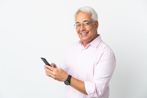 Brazylijski mężczyzna w średnim wieku na białym tle wysyłający wiadomość lub e-mail za pomocą telefonu komórkowego
