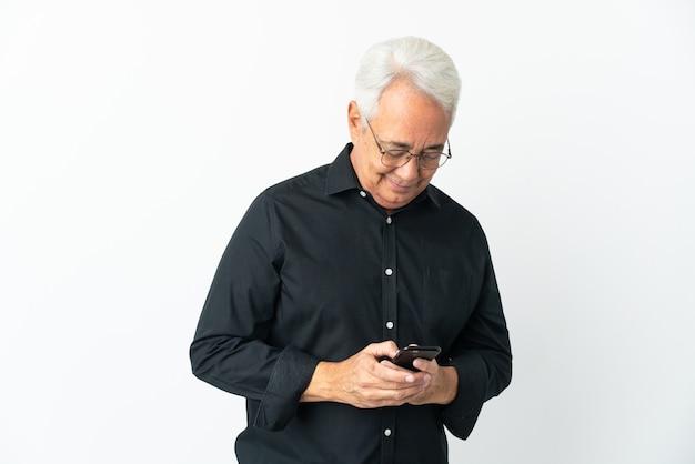 Brazylijski mężczyzna w średnim wieku na białym tle wysyłający wiadomość za pomocą telefonu komórkowego