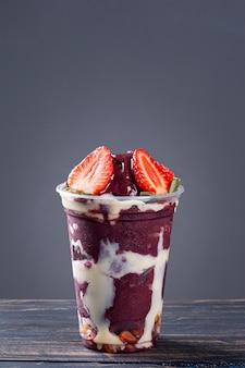 Brazylijski mrożony jogurt w plastikowym kubku ze skondensowanym mlekiem i truskawkami. owoce z amazonii. skopiuj miejsce