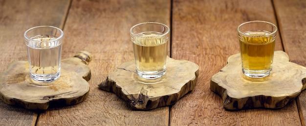 """Brazylijski napój destylowany, zwany """"pinga"""" lub """"cachaía"""", z rustykalnym drewnianym tłem, kopia przestrzeń"""