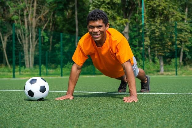 Brazylijski piłkarz rozgrzewa się, robi pompki i doskonali swoje umiejętności panowania nad piłką, trenując latem na boisku sportowym w parku.
