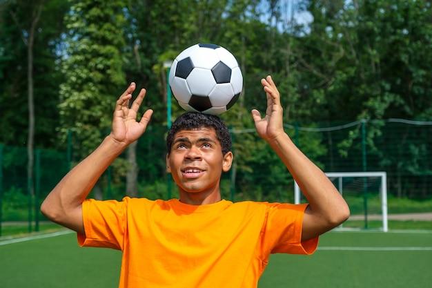 Brazylijski piłkarz trenuje i poprawia kontrolę nad piłką, latem żonglując nią na głowie na boisku sportowym