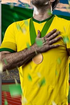 Brazylijski sportowiec zdobycie złotego medalu przed brazylijską flagą.