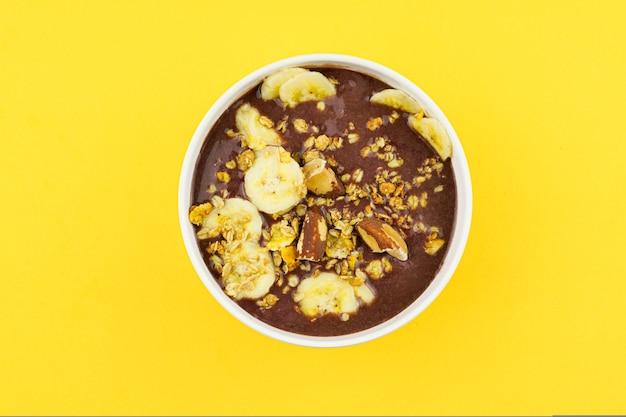 Brazylijskie aă§ai w białej misce z bananem, muesli i kasztanami.