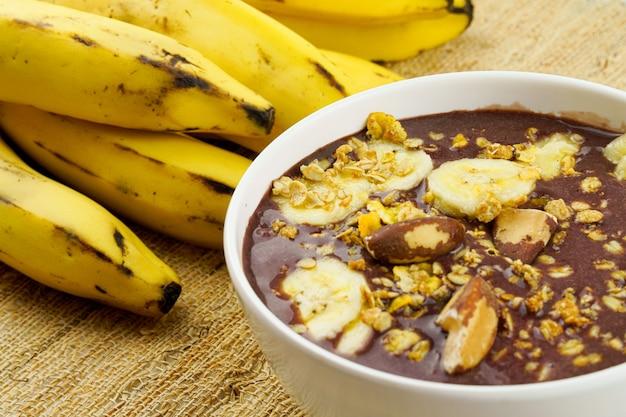 Brazylijskie aai w białej misce z bananową granolą i kasztanami widok z góry