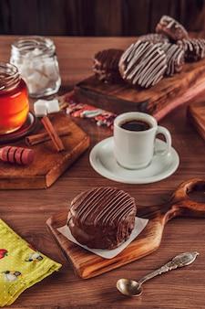 Brazylijskie ciasteczko z miodową czekoladą pokryte na drewnianym stole z kawą - pao de mel