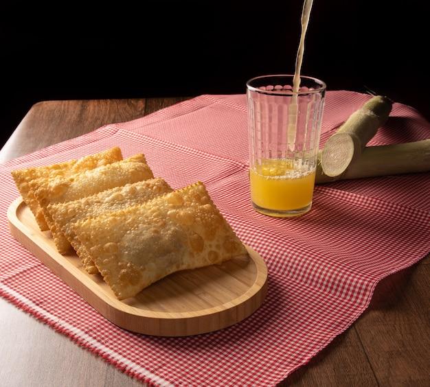 Brazylijskie ciastka smażone, szklanka soku z trzciny cukrowej i laski ułożone na obrusie w kratkę