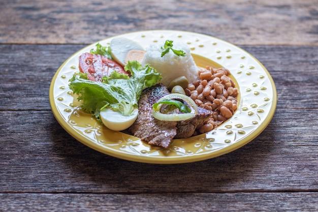 Brazylijskie danie kulinarne fasola ryżowa, mięso i sałatka.