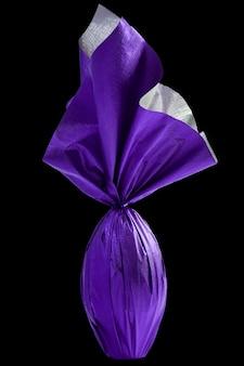 Brazylijskie jajko easters zawinięte w fioletowy papier na czarnej ścianie