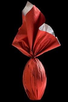 Brazylijskie jajo easters zawinięte w czerwony papier na czarnej ścianie