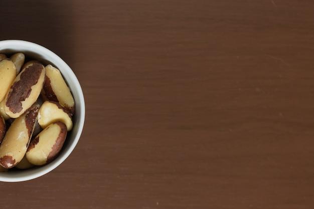 Brazylijskie orzechy w misce na drewnianym stole.