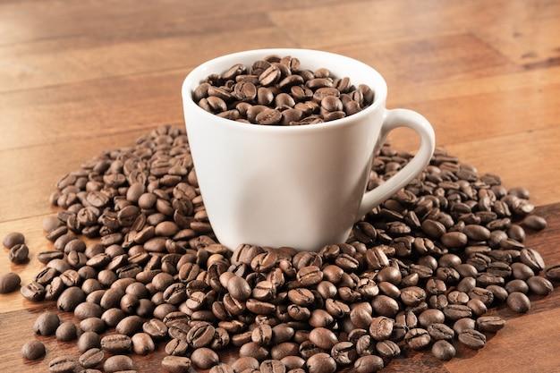 Brazylijskie ziarna kawy w filiżance i wokół niej