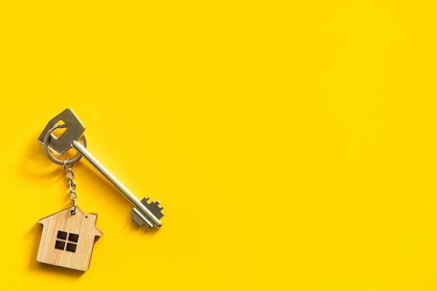Breloczek w kształcie drewnianego domku z kluczem na żółtym tle.