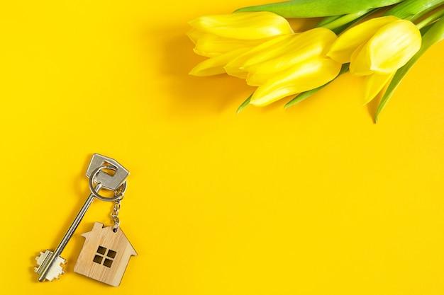 Brelok w kształcie drewnianego domku z kluczem na żółtym tle i wiosennymi tulipanami.