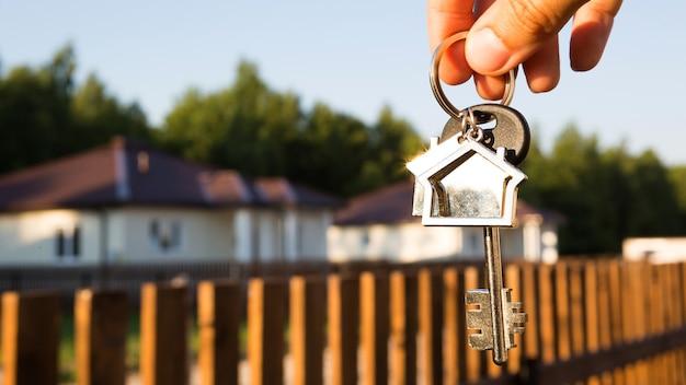 Brelok z breloczkiem w ręku. tło ogrodzenia i domku. przeprowadzka do nowego domu, kredyt hipoteczny, kupno nieruchomości, wynajem i rezerwacja mieszkania, marzenie o zamieszkaniu na wsi. skopiuj miejsce