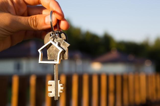 Brelok z brelokiem domek w ręce ogrodzenia i domku. przeprowadzka do nowego domu, kredyt hipoteczny, kupno