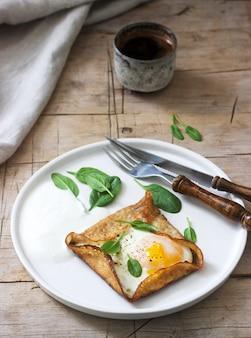 Bretońskie naleśniki gryczane z jajkiem, szpinakiem i śmietaną, wypełnione kawą. styl rustykalny.