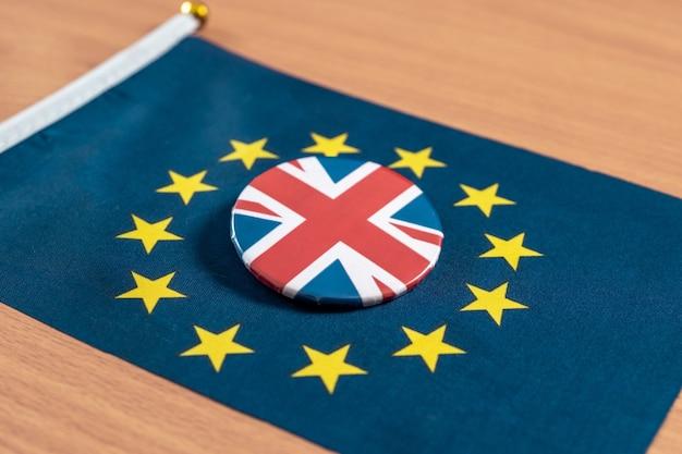 Brexit, flaga unii europejskiej z flagą wielkiej brytanii na ikonie kurtki razem na stole.