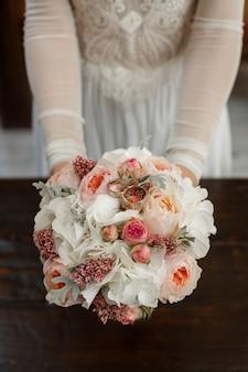 Bridal bukiet białe peonie i róże z obrączki ślubnej zbliżeniem. panna młoda trzyma obrączki i bukiet ślubny.