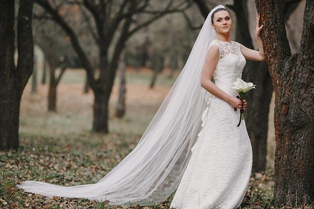 Bride opierając się na drzewie